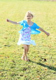 Twisting little girl. Twisting barefoot kid - smiling girl in dress with blue and lila flowers and blue t-shirt dancing on green meadow Royalty Free Stock Photography