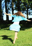 Twisting little girl. Twisting barefoot kid - smiling girl with flying hair dressed in blue skirt and blue t-shirt dancing on green meadow in front of shadowed Royalty Free Stock Photo