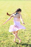 Twisting little girl. Twisting barefoot girl with long brunette braid in pink dress dancing on green meadow Stock Image