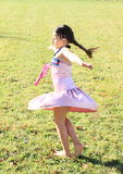Twisting little girl. Twisting barefoot girl with long brunette braid in pink dress dancing on green meadow Royalty Free Stock Image