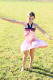 Twisting little girl. Twisting barefoot girl with long brunette braid in pink dress dancing on green meadow Royalty Free Stock Photo