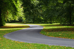 Twisting path road. A clear twisting path or road winds through trees, very green and verdant concepts: route path less traveled journey progress Royalty Free Stock Photography