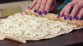 Twisting pita bread with a filling of greenery and cheese stock footage