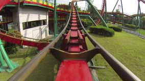 Twisting red and yellow roller coaster stock video footage