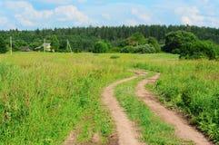 Twisting road  to village near wood Stock Photo