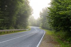 Twisting road in the foggy morning stock photography