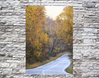 Twisting road  in a window behind a stone wall Stock Photo