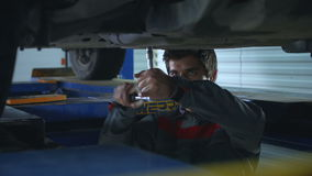 Twisting the screws. Mechanic twisting the screws under the car stock video