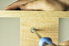 Installing a threaded furniture fastener. Twisting the threaded furniture fastener into the socket royalty free stock photography