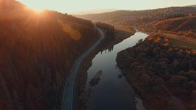 Twisty riverbed. The road parallel to the river. Amazing places. Aerial: Beautiful sunset in the highlands. Forest, country road and the river bed at sunset stock video