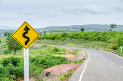 Twisty road with road-sign Stock Images