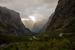 Twisty Road to Milford Sound Surrounded by Mountains. The twisty road to Milford Sound, cloudy sky, sun just breaking through.nnSouth Island of New Zealand Stock Photography