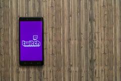 Twitch логотип на экране smartphone на деревянной предпосылке Стоковые Фотографии RF