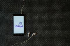 Twitch logo on smartphone screen. Los Angeles, USA, october 23, 2017: Twitch logo on smartphone screen and earphones plugged in on metal plate background Stock Images