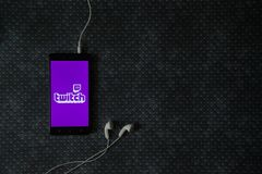 Twitch logo on smartphone screen. Los Angeles, USA, october 23, 2017: Twitch logo on smartphone screen and earphones plugged in on metal plate background Royalty Free Stock Photos