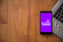 Twitch. Los Angeles, USA, april 16, 2017: Twitch application on smartphone with earphones and notebook on wooden background Royalty Free Stock Photo