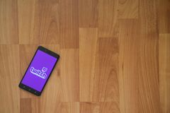 Twitch on smartphone screen. Los Angeles, USA, july 18, 2017: Twitch on smartphone screen placed on the laptop on wooden background Royalty Free Stock Photo