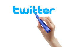 Twitter. Hand with blue marker drawing the twitter isolated on white background stock image
