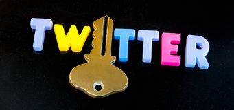 Twitter holds the key. Text `twitter` in bold uppercase letters with the letter `i` replaced by a gold key, dark background stock photo