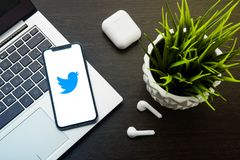 Twitter logo on the iphone X screen is placed on the laptop keyboard next to AirPods. Tula, Russia, May 1, 2019: Twitter logo on the iphone X screen is placed on stock image
