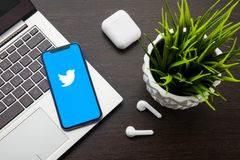 Twitter logo on the iphone X screen is placed on the laptop keyboard next to AirPods. Tula, Russia, May 1, 2019: Twitter logo on the iphone X screen is placed on stock photo