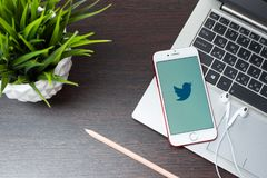 Twitter logo on the iphone screen is placed on the laptop keyboard next to EarPods in the office. Tula, Russia, March 12, 2019: Twitter logo on the iphone screen stock photography