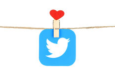 Twitter logo, printed on paper, hangind on a rope with red heart Stock Photo