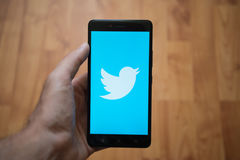 Twitter logo on smartphone screen. London, United Kingdom, june 5, 2017: Man holding smartphone with Twitter logo on the screen. Laminate wood background stock photography