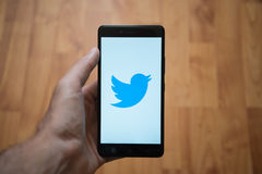 Twitter logo on smartphone screen. London, United Kingdom, june 5, 2017: Man holding smartphone with Twitter logo on the screen. Laminate wood background Royalty Free Stock Images