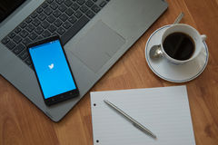 Twitter. Nitra, Slovakia - march 28, 2017: Twitter application in a mobile phone screen. Workplace with a laptop, an earphones, notepad, pen and coffee on wooden Stock Images