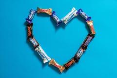 Twix,银河,窃笑,富饶,在蓝色背景的火星普遍的微型糖果巧克力块在心形 概念亲吻妇女的爱人 免版税库存图片