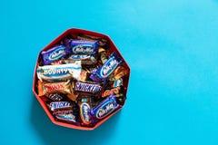Twix, droga mleczna, Snickers, nagroda, Mąci popularnego mini cukierku czekoladowych bary na błękitnym tle w pudełku obraz royalty free