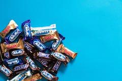 Twix, manière laiteuse, ricanements, générosité, barres de chocolat populaires de sucrerie de Mars mini sur le fond bleu avec l'e photo stock