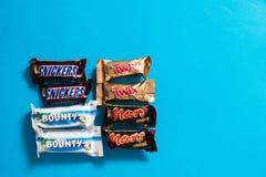 Twix, ricanements, générosité, barres de chocolat populaires de sucrerie de Mars mini sur le fond bleu photo stock