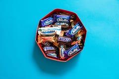 Twix, Via Lattea, risatine, bontà, barre di cioccolato popolari della caramella di Marte mini su fondo blu in scatola fotografie stock