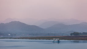 Twlight Landscape. A boat on the river at evening, twilight and mountain view Stock Image