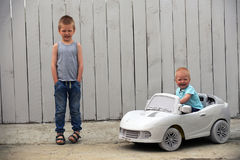 Two сute little dude plays with a toy car. On a rural farmstead in a hot summer royalty free stock photography