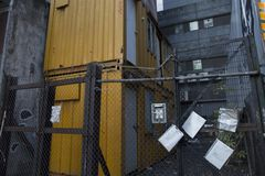 Two yellow containers on grey. Two abandoned bright yellow containers behind a wire fence with eviction notices Royalty Free Stock Photo