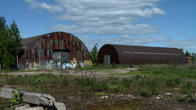 Two abandoned hangars. View on Two old hangars at summer day stock video footage