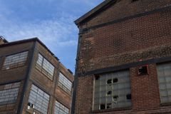 Two abandoned industrial buildings against a blue sky. Horizontal aspect royalty free stock image