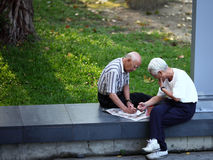Two absorbed seniors. Men sitting on  the fence in park Royalty Free Stock Image