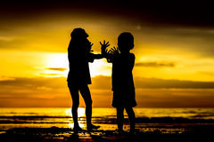 Two abstract kids silhouettes at sunset. Two abstract silhouettes of unrecognizable kids playing at the beach at sunset royalty free stock photography