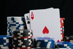 Two aces, close-up, surrounded by a big bet in a casino gambling, on a black background royalty free stock photos