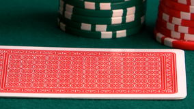 Two aces. Of diamonds and club aces in a hand on a green cloth stock footage