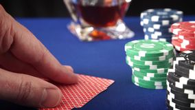 Two aces in hand and Gambling chips on casino blue felt. Gambling chips and poker cards in casino stock video