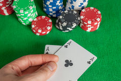 Two Aces and poker chips stack on green table Stock Photo