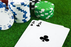 Two aces and some pokerchips. On green table Stock Photo