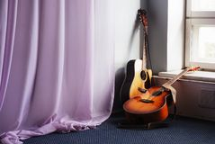 Two acoustic guitar next the window. And drapery Royalty Free Stock Photo