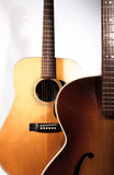Two acoustic guitars. Showing two classic acoustic guitars standing together one behind the other Stock Images