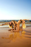 Two acrobatic girl on the beach Stock Photos